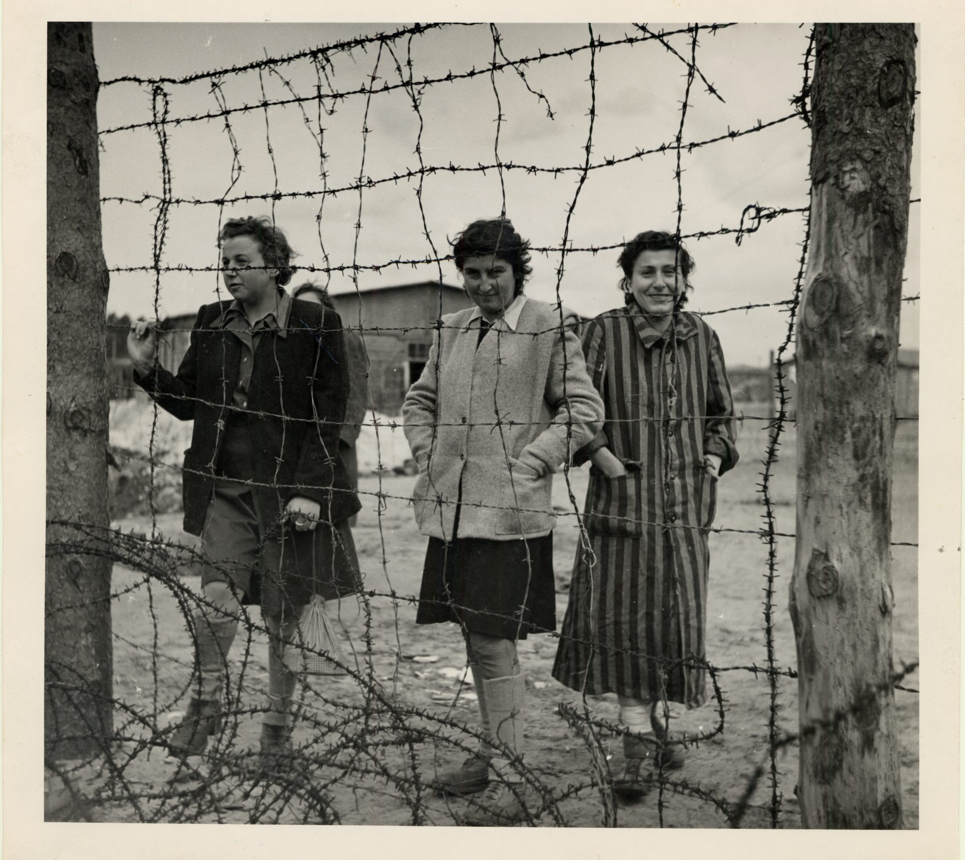 Three women standing behind a barbed wire fence at the Bergen-Belsen concentration camp after liberation. Germany, 1945.