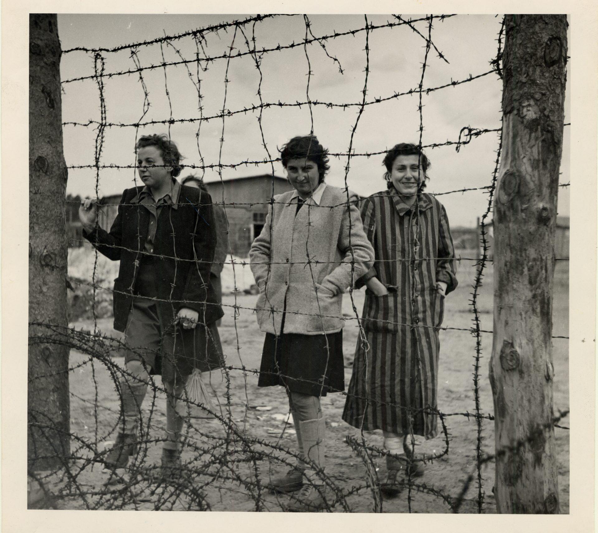 Trois femmes derrière les barbelés au camp de Bergen-Belsen, 1945.