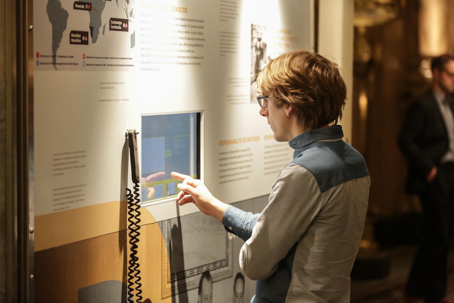 """L'exposition itinérante """"Ensemble contre le génocide : comprendre, questionner, prévenir"""" contient un système multimédia permettant la diffusion de témoignages, des entrevues avec des experts et des lignes du temps."""