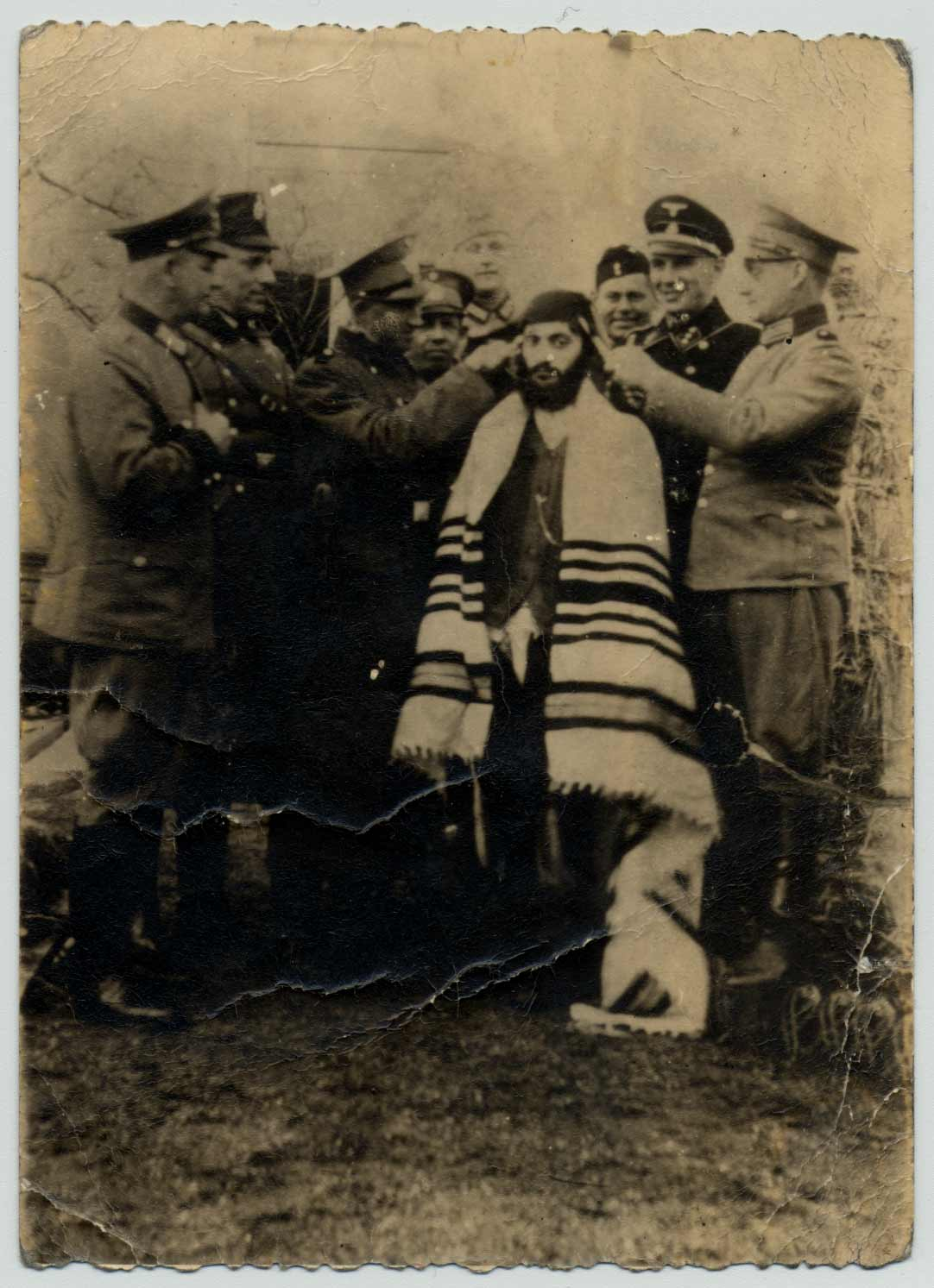 A Jewish man is humiliated by Nazi soldiers who are cutting his beard.