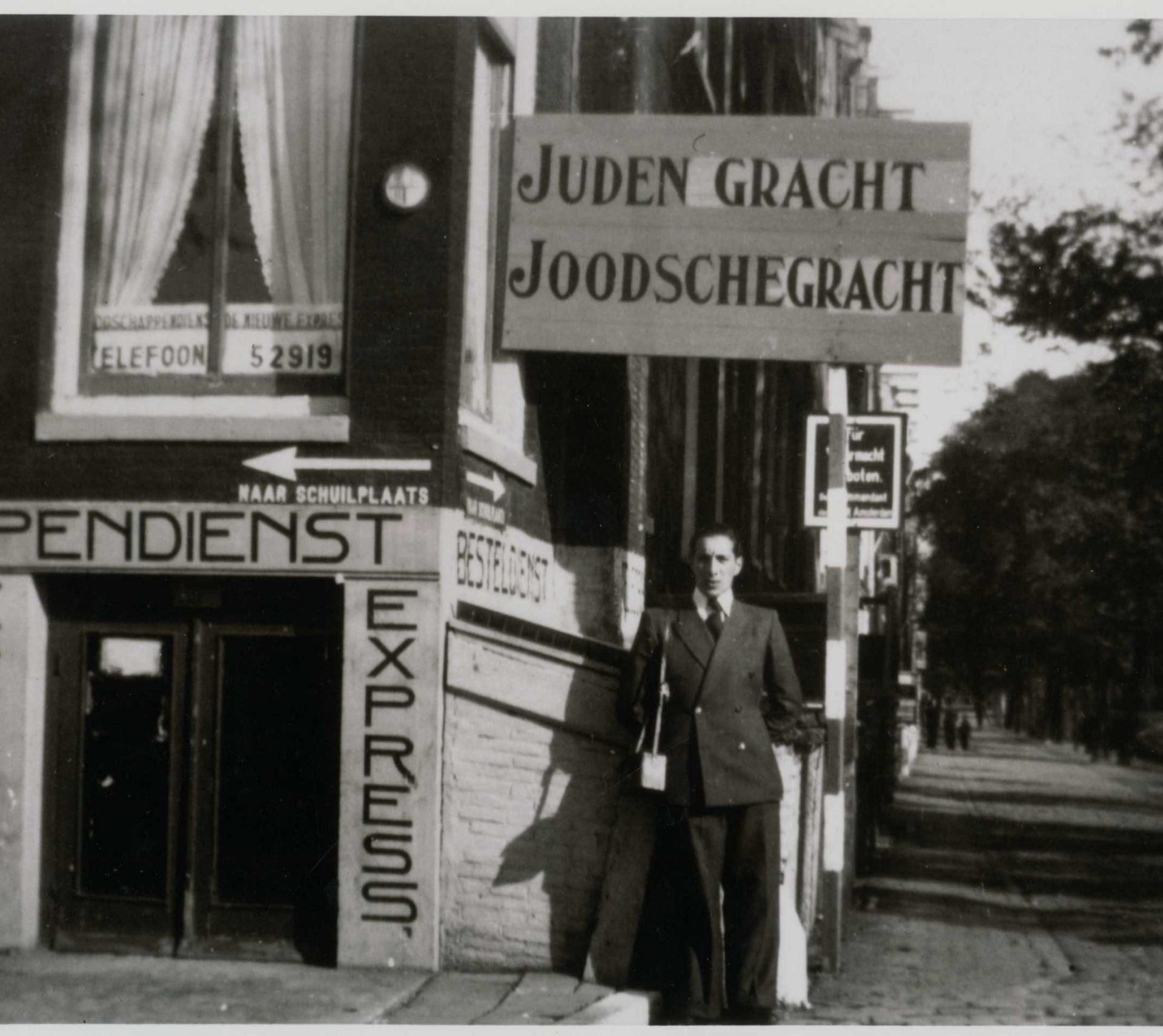 Photo de Sam Shryver sous les affiches indiquant les limites du quartier Juif. On y lit « Canal juif », en référence à la géographie de la ville d'Amsterdam, traversée de canaux.