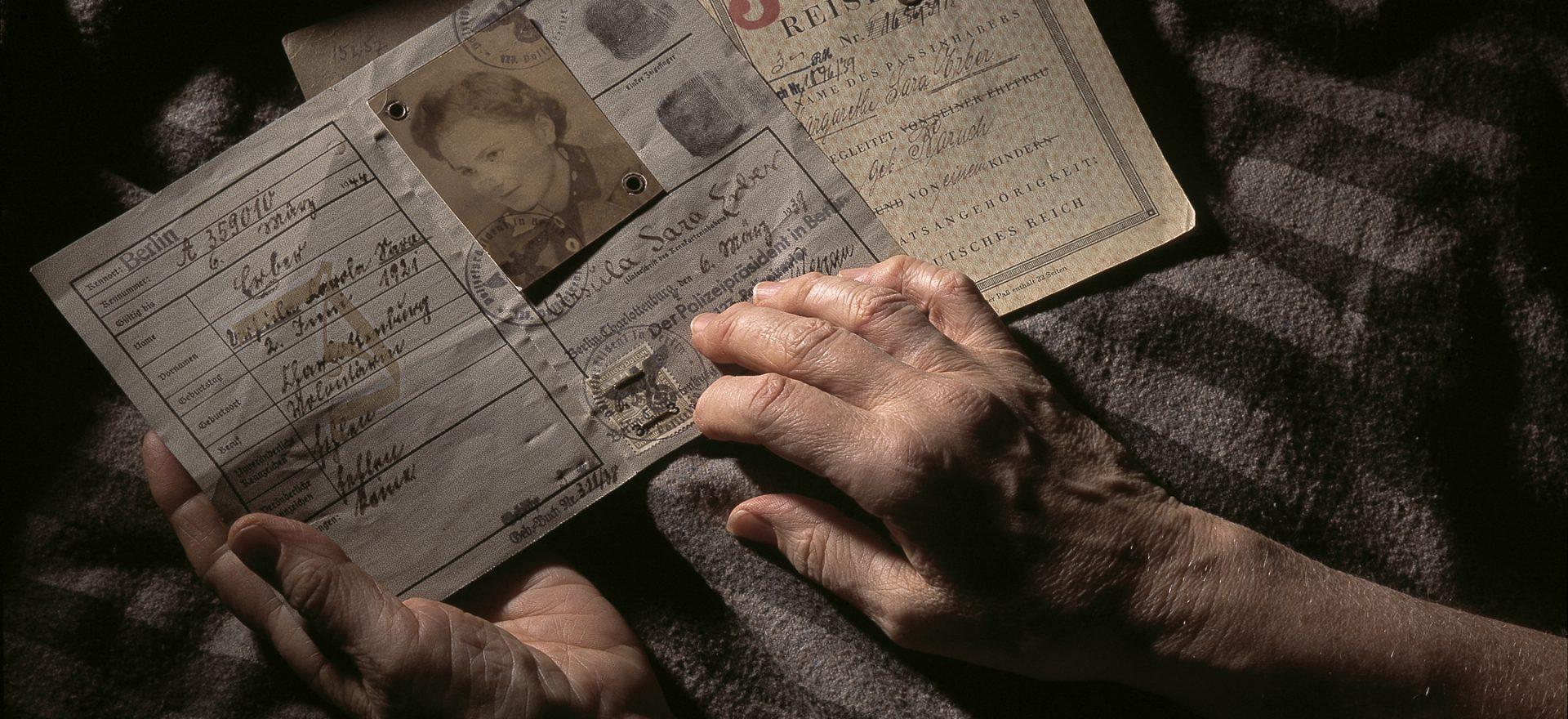 Les mains d'une personne âgée manipule des documents d'identité. Photographie illustrant la présentation, des fiches d'analyse des sources primaires, ressource éducation du Musée de l'Holocauste.