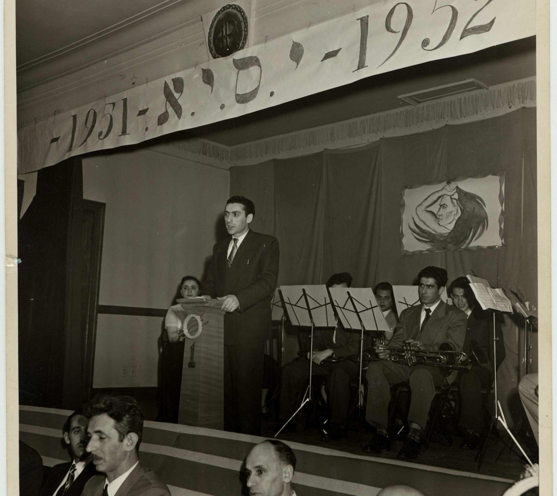 Photographie prise à Montréal en 1952 à l'occasion du premier anniversaire de la création de l'orchestre Zukunft. Avrum Feigenbaum prononce un discours sur la scène.
