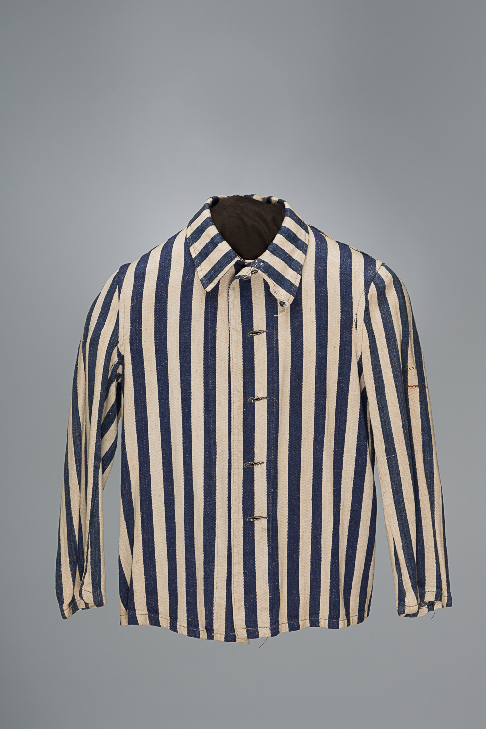 Upon arrival in the camps, women and men were forced to undress and their personal belongings were taken away. Prisoners selected for forced labour received a uniform like this one.
