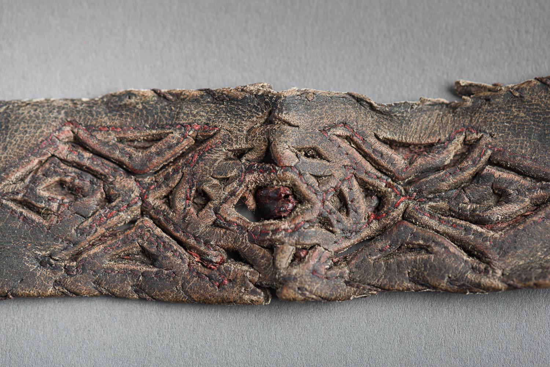 Ce bracelet est fait de cuir embossé et est brodé d'un fil rouge. (Photo : Peter Berra)