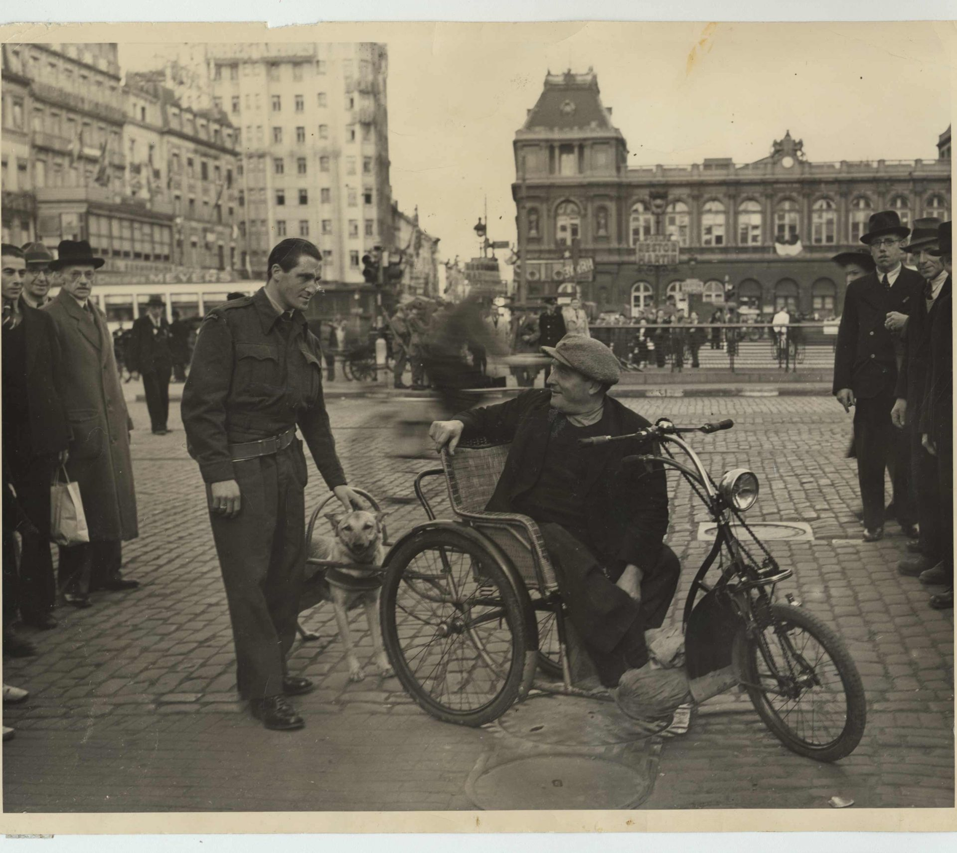 Saul Stein photographed in uniform in Brussels with a man on a tricycle in 1945.