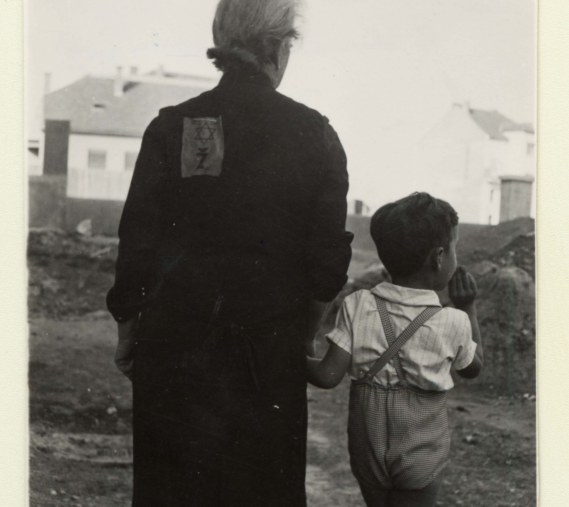 Emil Svarc and his grand-mother, from behind, wearing the yellow badge on her dress.