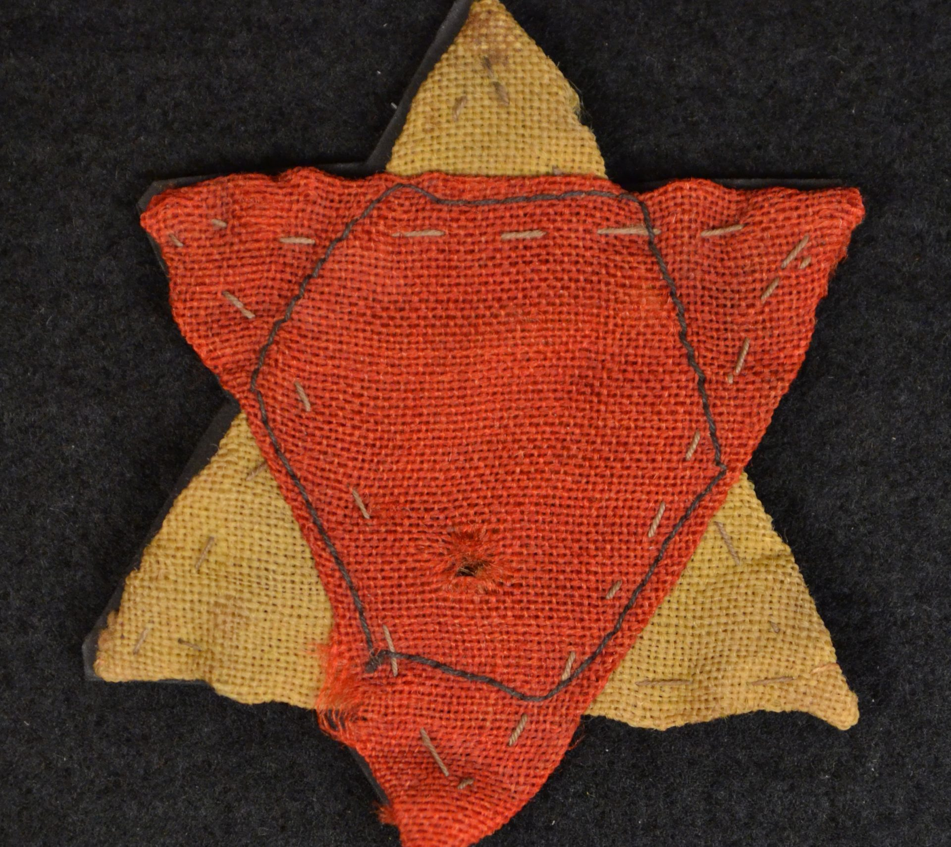 A Jewish political prisoner's identification badge, made of a yellow triangle and a red triangle. (Donated by Ilona Lindenfeld)