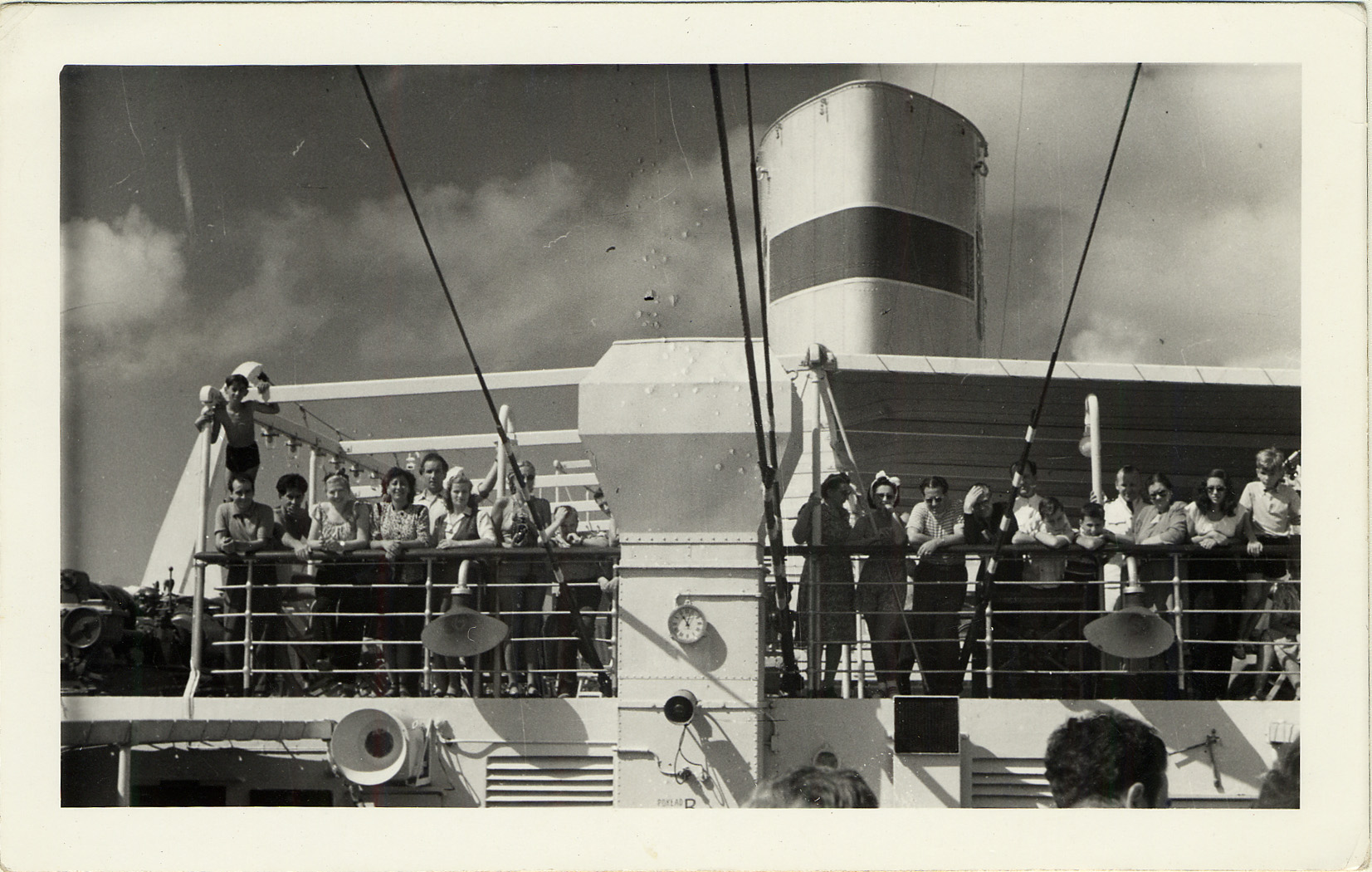 A group of men, women and children stand on the Serpa Pinto ship's balcony.