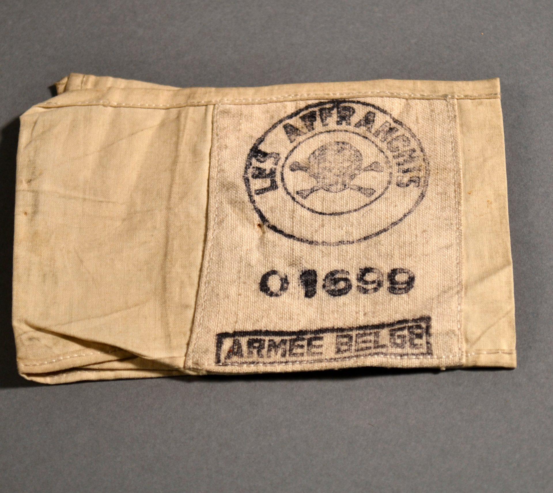 Son numéro de matricule 01699 est imprimé sur ce brassard avec le logo du groupe Les Affranchis.