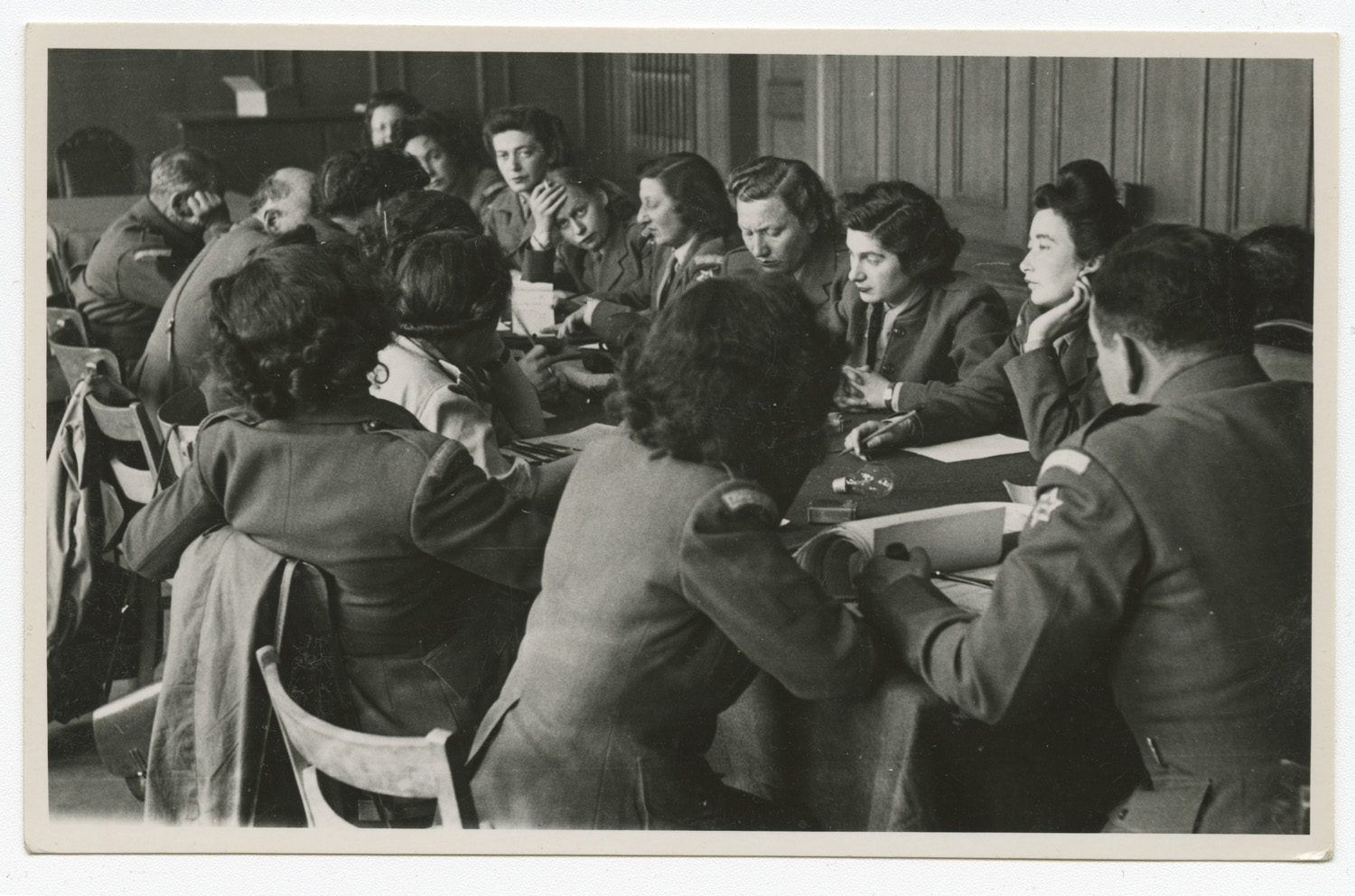 A metting of the Council of Voluntary Agencies held in Munich. The table is surronded mostly by women and Marie Malachowski is fourth from the top-right.