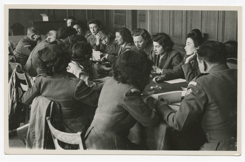 Une rencontre du Council of Voluntary Agencies qui se déroule à Munich. Une majorité de femmes sont assises autour de la table et Marie Malachowski est la 4e à partir de la droite.