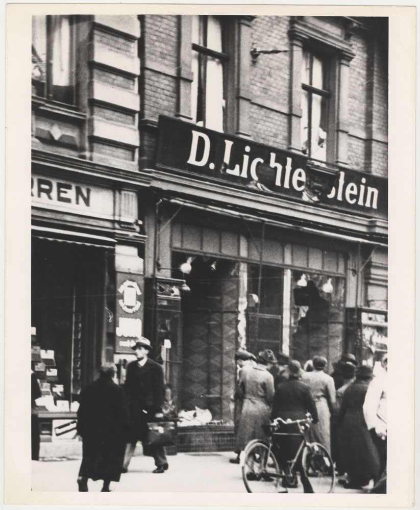 "This photograph shows a Jewish storefront that was vandalised during Kristallnacht. People are looking inside the broken window under the name ""D. Lichtenstein""."