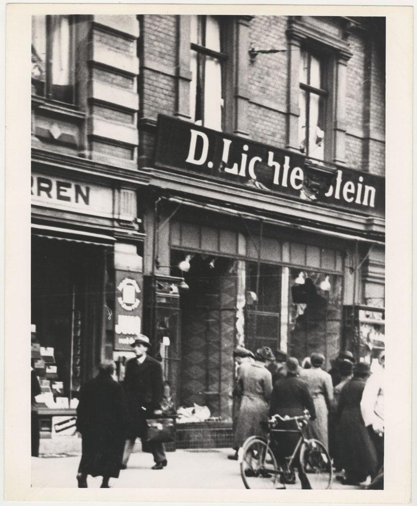 Cette photographie montre une devanture de magasin juif vandalisée au cours de Kristallnacht. Des passants regardent à l'intérieur d'une vitrine brisée sous l'écriteau ''D. Lichtenstein''.