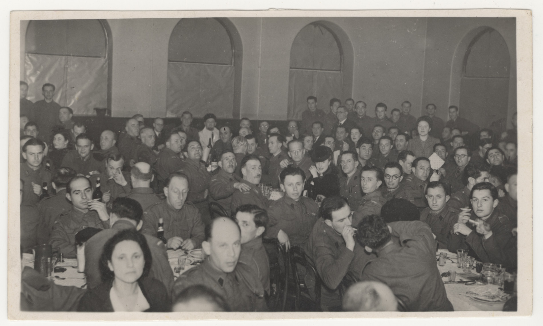 This photograph depicts Polish soldiers, accompanied by women and other civilians, at a dinner for Passover, an important Jewish holiday. Willie Glaser is in front of the standing group on the far right of the picture, wearing glasses.