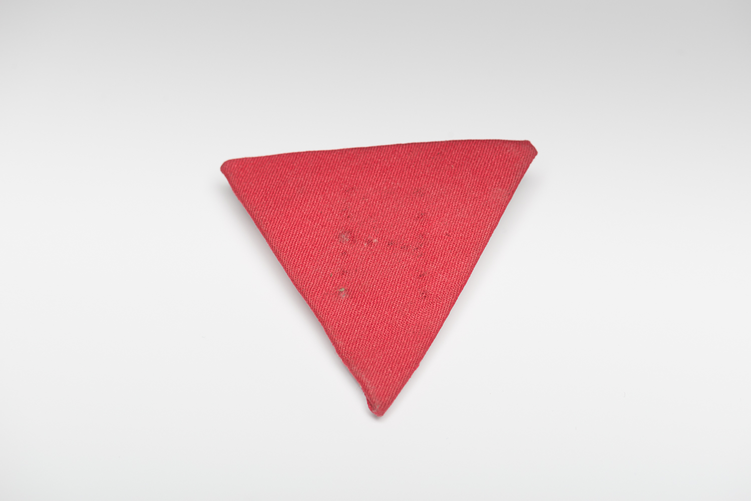 This red triangular identification badge was used to identify political prisoners in Nazi concentration camps.