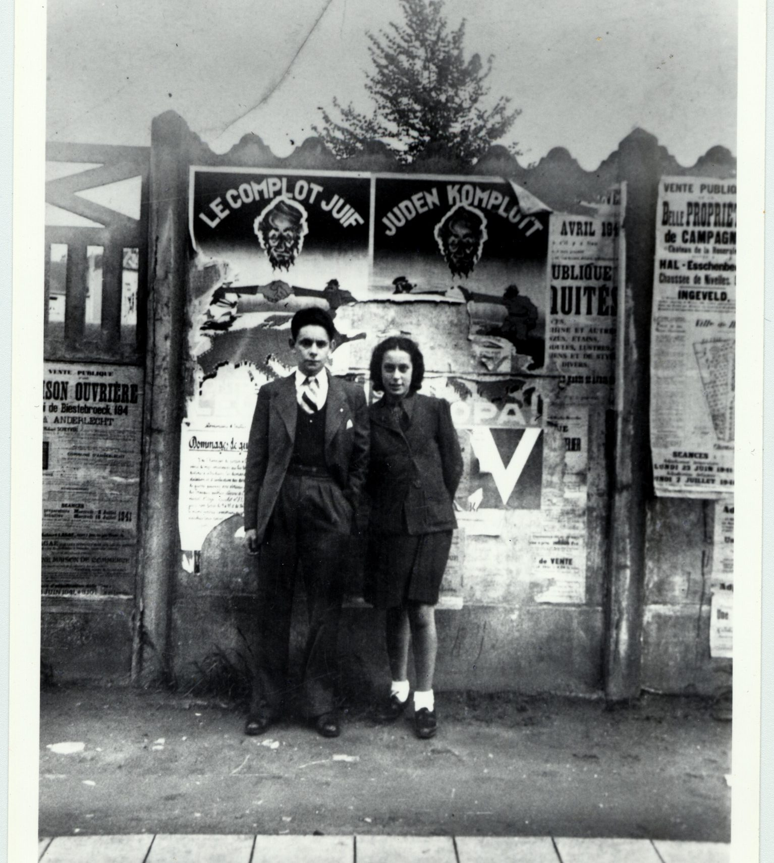 "Walter and his sister Liese in Belgium in front of an antisemitic poster saying ""The Jewish Conspiracy"" in 1941."