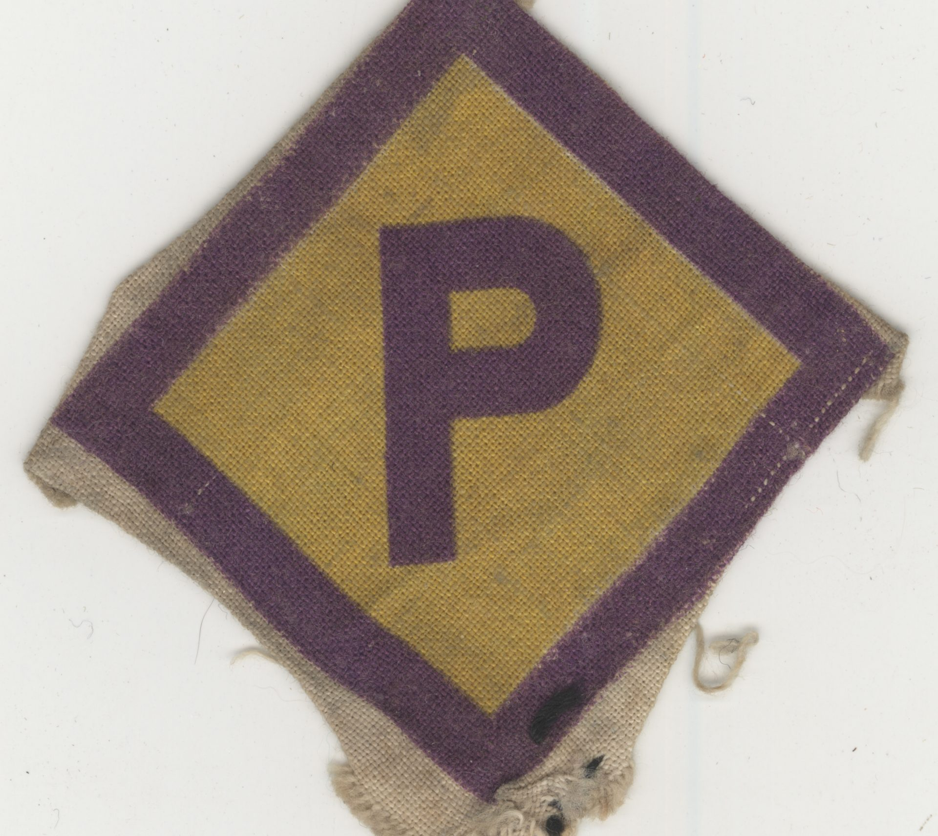 Yellow diamond-shaped badge used to  identify Polish labourers working in Germany during the war. This badge belonged to Aba Beer.
