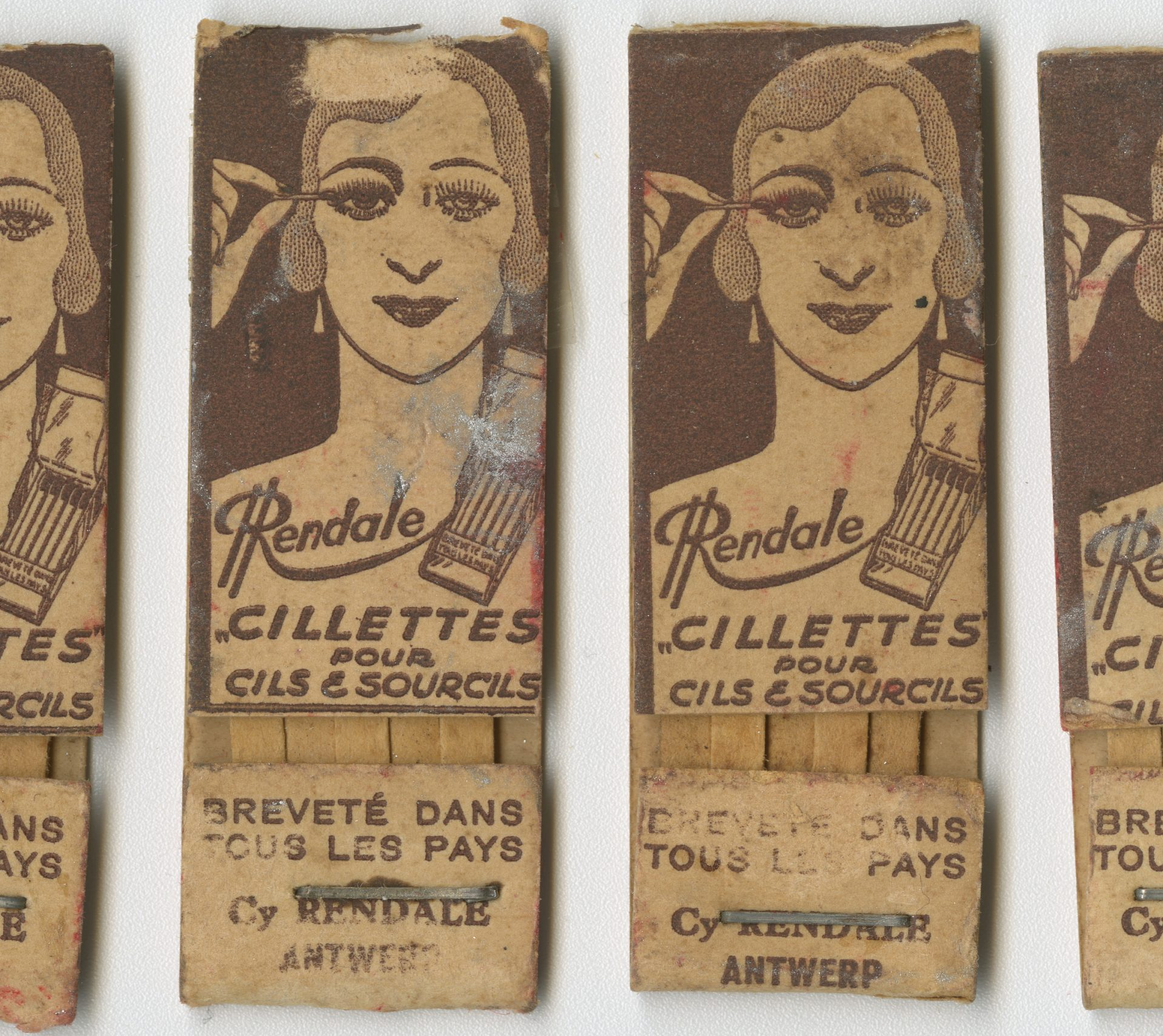 Ce carton de cosmétique contient des ''cillettes'', un maquillage pour les cils et les sourcils. Il s'agit de petites allumettes en carton à l'embout empreint d'un fard brun pour maquiller les yeux.