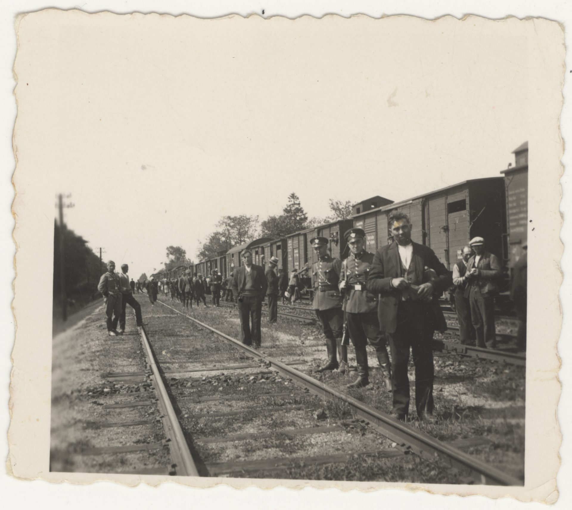 Photograph was probably taken in the Lodz ghetto in 1944. Men stand on train rails and two of them wear a police uniform. There are cattle cars in the background, which Jews were forced to board during deportations.