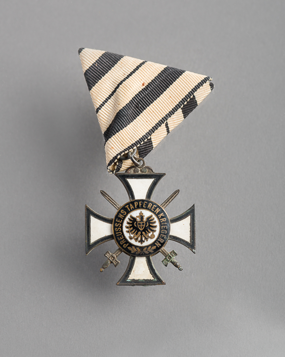 "Medal received by Sandor Vadasz, a Jewish veteran. Two swords meet at the centre of a cross with a German imperial eagle. The words Preussens Tapferen Kriegern ""To Prussia's Brave Soldiers"" are written on the front of the medal. (Photo: Peter Berra)"