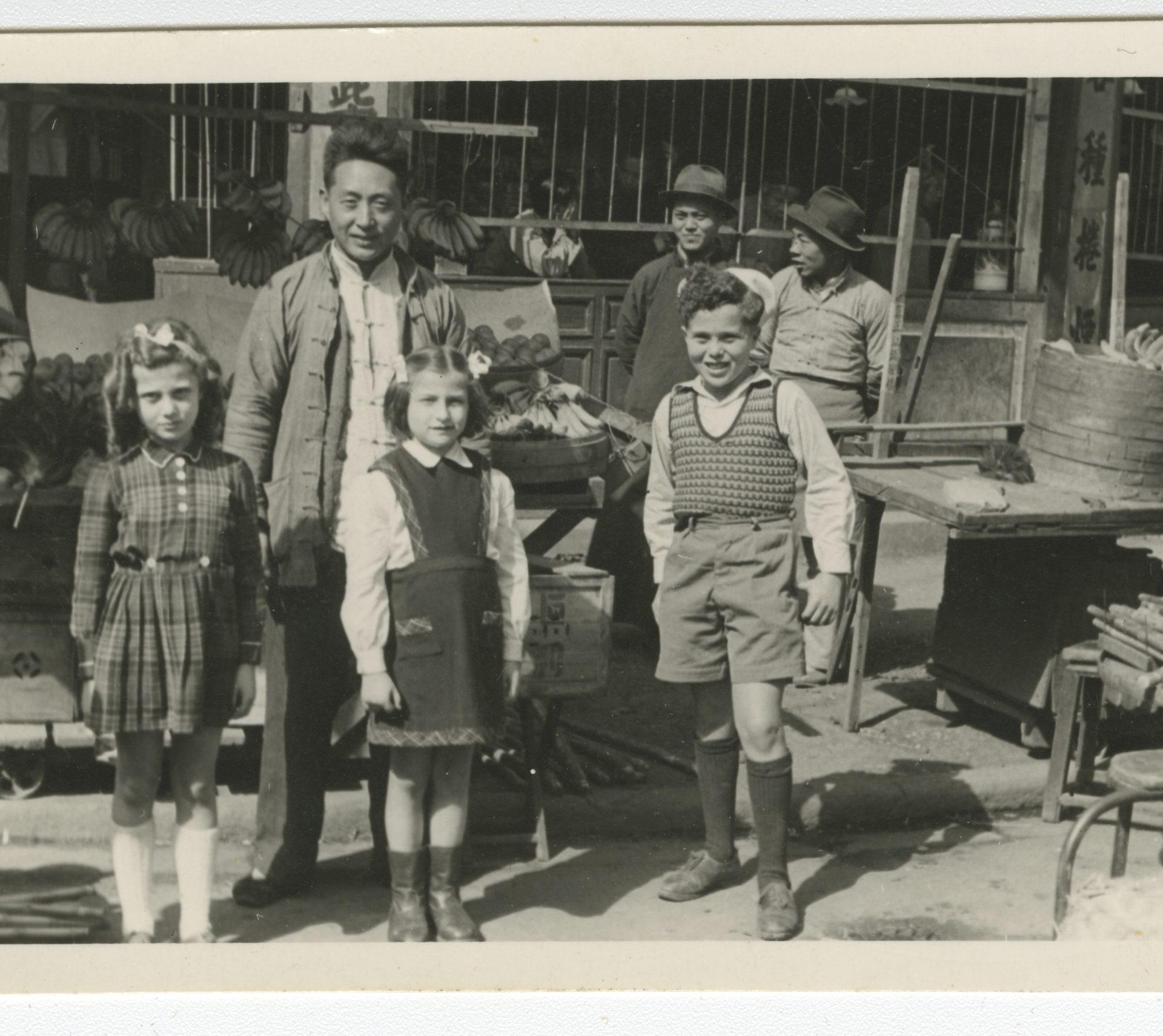 Photograph of the children Vera Voticky, Eva Kanturek and Milan Voticky stand in a local market in Shanghai.