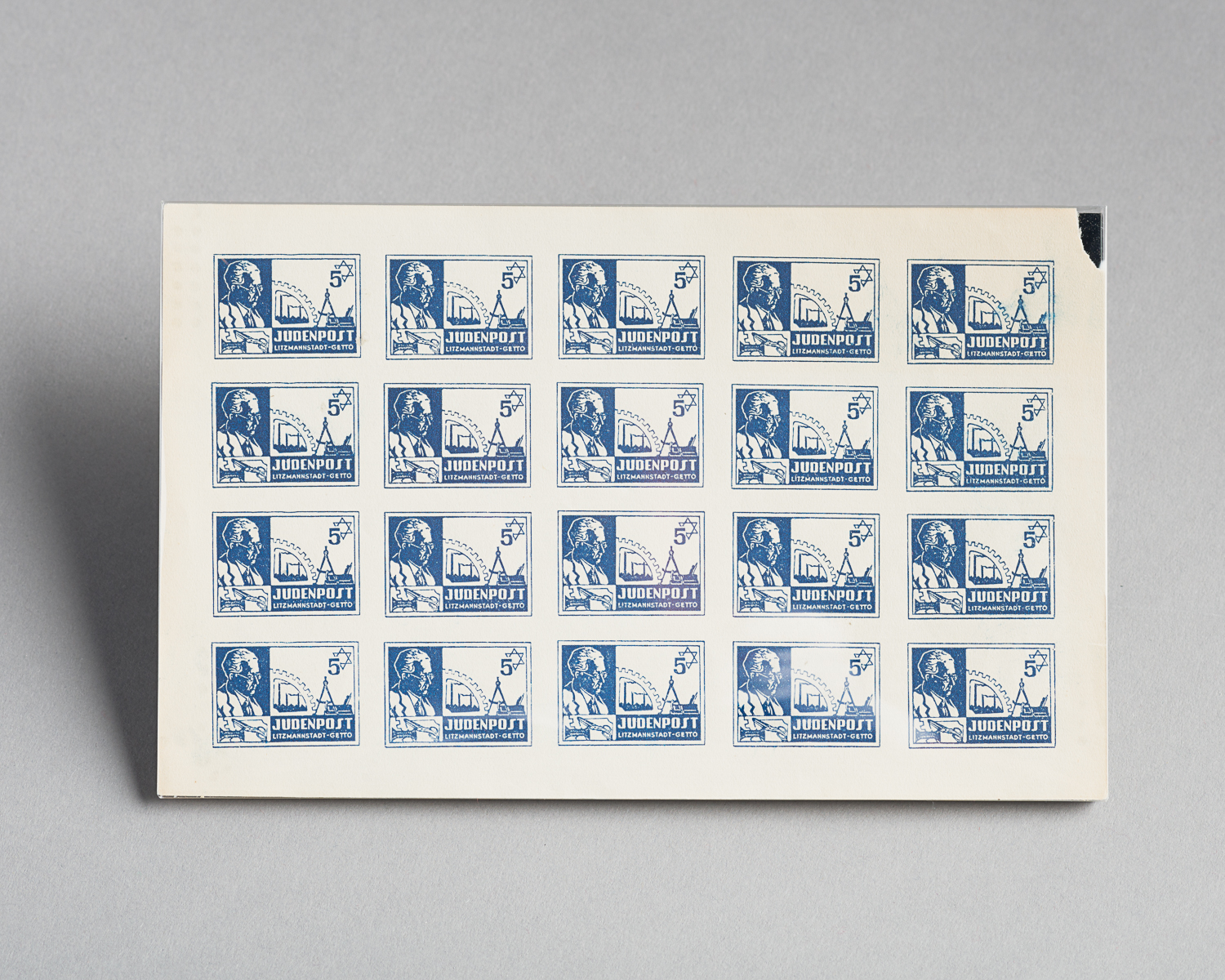 This sheet of postage stamps was printed by the Lodz ghetto Judenrat in Poland. Each of the twenty stamps includes the Star of David, a compass, scissors and a wheel. The profile of Mordechai Chaim Rumkowski, Head of the Lodz ghetto Judenrat, is printed on the left side. (Photo: Peter Berra)