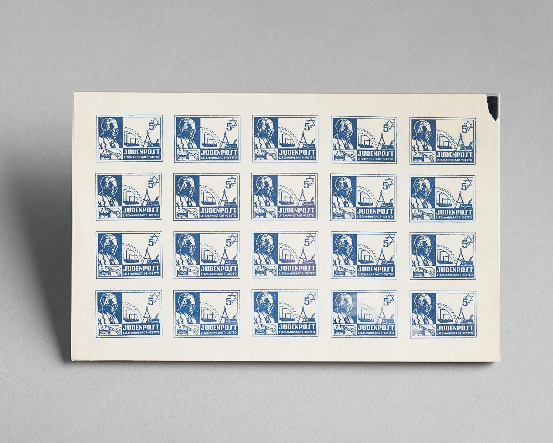 Cette feuille de timbres fut imprimée à l'encre bleue par le Judenrat du ghetto de Lodz, en Pologne. Sur chacun de ces vingt timbres, les symboles de l'étoile de David, un compas, une paire de ciseaux et une roue sont représentés. Le profil de Mordechai Chaim Rumkowski, le dirigeant du Judenrat du ghetto de Lodz (Litzmannstadt), est également représenté sur la gauche de l'image. (Photo : Peter Berra)