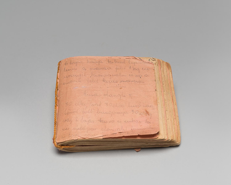Livre de recettes composé de papiers récupérés dans l'usine où travaillait Edith Gluck. Ils sont reliés par une ficelle, également trouvée dans l'usine du camp. Près de 200 recettes sont écrites dans ce livret qu'Edith a caché au camp de Lippstadt, en Allemagne. (Photo : Peter Berra)