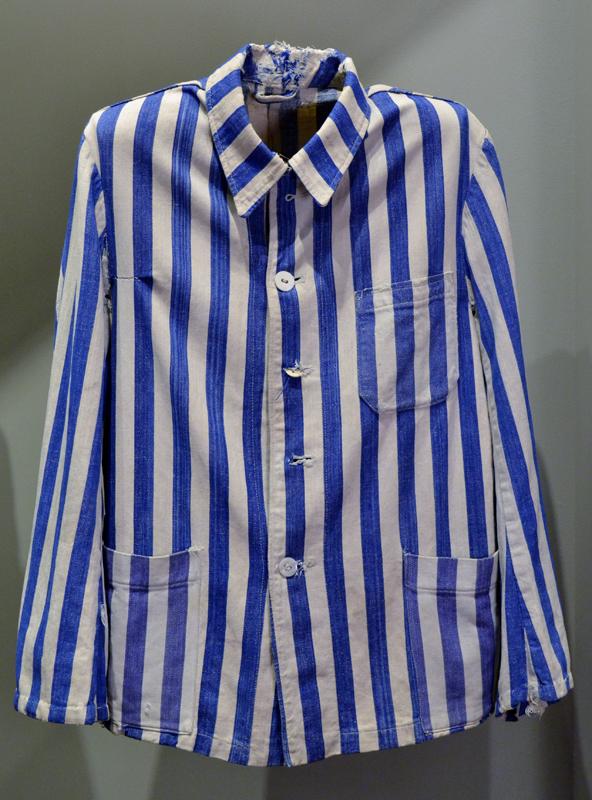 Veste d'uniforme de prisonnier ayant appartenue à Zigmund Schick. Faite de coton, rayée de blanc et de bleu cobalt, elle compte trois poches, taillées dans le même tissu rayé, et cinq boutons blancs. Dans les camps de concentration, les prisonniers doivent porter un vêtement qui les distingue des civils ou des militaires.