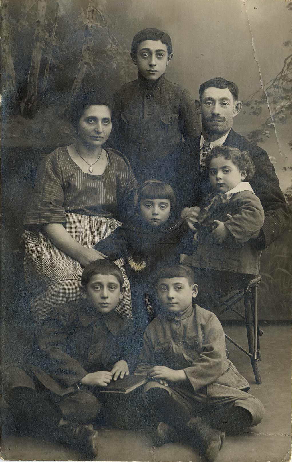 A portrait of the Feigenbaum family, Lodz, 1921. Avrum, as a child, sitting on the lap of his father Icak. He is surrounded by his mother Cyna, his sister Mindl, and his brother Eli standing in the back. His brothers Hersh and Mordechai sit in the front. Of the whole family, only Avrum and Hersh survived the Holocaust.
